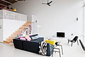 Grey corner sofa in modern living room of loft apartment with white floor