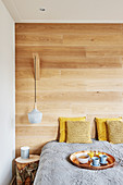 Double bed against wooden wall