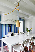 White dining table and chairs below pendant lamp and wood-burning stove against blue-striped wallpaper