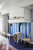 Wood-burning stove against blue-striped wallpaper in dining room
