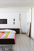 Double bed with striped bedspread in white bedroom with wooden floor