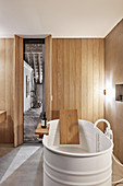 Free-standing bathtub in bathroom with wood-clad walls