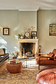 Open fireplace and leather armchair in sunny living room in earthy shades