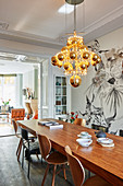 Modern chandelier of golden spheres above dining table in period building