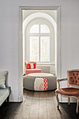 Open doorway leading into living room with ottoman and armchair below arched window