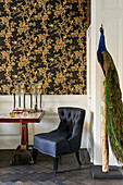 Stuffed peacock on post in seating area with black and gold floral wallpaper