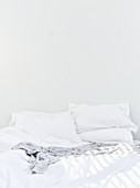 Double bed with whit bed linen against white wall