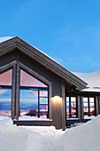 Modernes Holzhaus vor blauem Himmel im Schnee