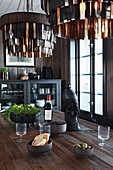 Leather-fringed lampshades above raven figurine on dining table
