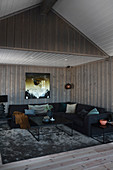 Black corner sofa in dark living room with wood-panelled walls and ceiling