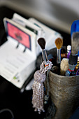 Pot of paintbrushes and beaded tassel on desk