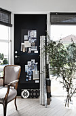 Baroque chair, black pinboard on door and olive branches in floor vase in study