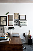 Wooden desk below various prints on wall