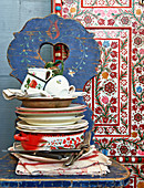 Crockery stacked on farmhouse chair in front of ethnic wall panel
