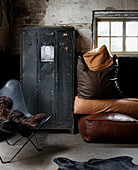 Industrial-style furnishings: black locker, leather cushions and classic Butterfly Chair