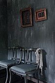 Two chairs below framed pictures on black wall
