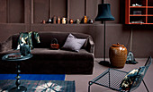 Brown sofa below ornaments on ledge in brown wall