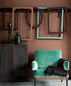 Turquoise armchair, wooden cabinet and picture frames on dusky pink wall