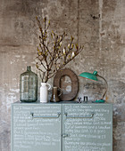 Metal cabinet decorated with handwriting, vase of twigs, decorative letter and table lamp