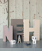 Pastel decorative letters made from old books in front of wooden wall
