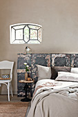 Double bed with vintage panel used as headboard