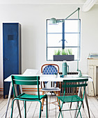 Dining table and various garden chairs with blue metal locker in background