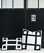Black-and-white cushions in front of black metal door
