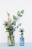 Eucalyptus, Eryngo, and waxflower in glass bottles