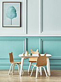 Kinderstühle mit Ohren am Tisch vor zweifarbiger Kassettenwand