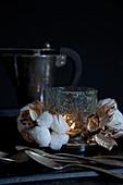 Baumwollkapseln um ein Windlicht aus Glas vor schwarzem Hintergrund