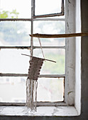 Macramé ornament hung from branch in front of window
