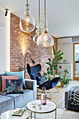 Gläserne Deckenleuchten im Wohnzimmer mit Backsteinwand