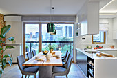 Wooden table and grey upholstered chairs next to open-plan kitchen