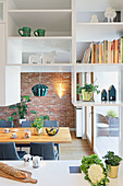 Suspended shelving used as partition between kitchen and dining room
