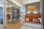 Upholstered bench and mirrored wall in elegant hallway