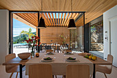 Set table in front of glass wall overlooking terrace of architect-designed house
