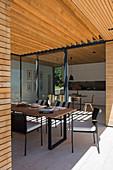 Esstisch auf überdachter Terrasse am modernen Architektenhaus