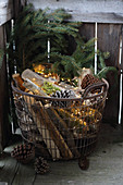 Firewood, pine cones and fairy lights in wire basket