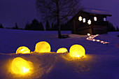 Ice candle lanterns lying in snow in front of illuminated path leading to cabin