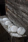 LED candles in ice candle lanterns on rustic wooden bench outside cabin