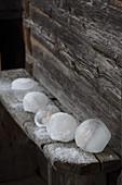 Windlichter aus Eis mit LED-Lichtern auf rustikaler Holzbank an der Hütte