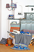 Knitted textiles with classic patterns around tiled stove