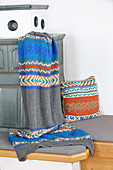 Knitted blanket and cushion with Norwegian pattern on bench of tiled stove