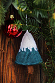 Knitted decoration in shape of Christmas tree hung from conifer branch