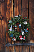 Christmas wreath decorated with knitted fir trees, gnomes and houses