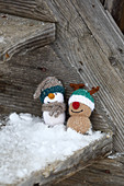 Knitted winter decorations in shapes of snowman and reindeer on rustic wood