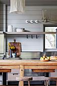 Blick über Esstisch aus Holz auf Küchenregal