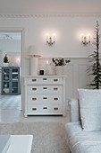 Antique chest of drawers in white living room with wintry decorations