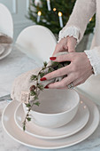 Hands placing napkin and larch branch on set table