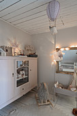 Antique sideboard in vintage-style nursery decorated in grey